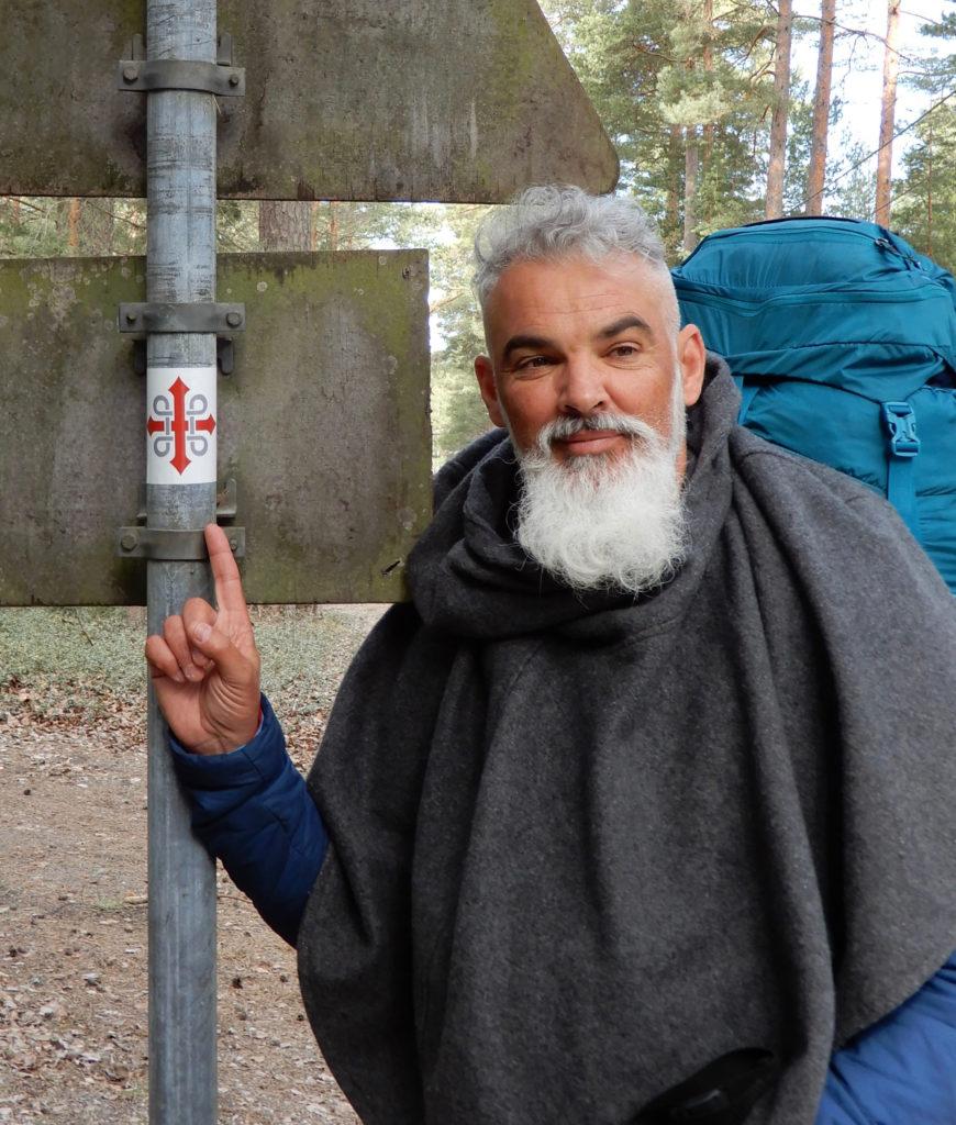 En man med långt, vitt skägg och stor ryggsäck på ryggen